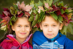 Two Kids wearing Wreath of Leaves. Portrait of a boy and a girl wearing wreathes of fall leaves royalty free stock photo