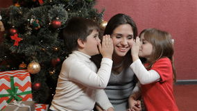 Two kids wisper into woman`s ears near the christmas tree stock video