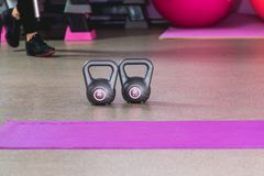 Two kilos in a grey colour weights in a sport studio with pink balls on the backround and sneakers.  royalty free stock photo