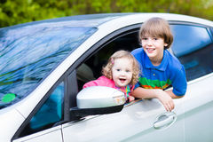Two kinds enjoying a car ride on a summer day Stock Images