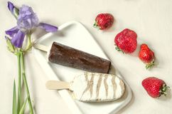 Two kinds of ice cream on a stick  with chocolate lie on a white plate, near a branch with purple iris and strawberries Royalty Free Stock Photos