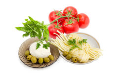 Two kinds of mozzarella cheese, olives, tomatoes and potherb. Ball of the fresh mozzarella cheese on the glass saucer, mozzarella cheese twisted to form a plait Stock Photos