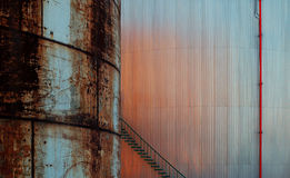 Two kinds of oil tanks. Location: Montreal, Quebec, Canada. Lens: Kikkor 50 mm. Look at the nice orange light produced by the sun between the tanks Royalty Free Stock Photography