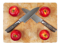 Two kinfes crossed on chopping board with apples Stock Photo