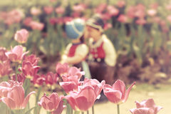Two kissing dolls in tulip garden. Royalty Free Stock Photography