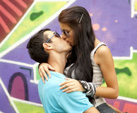 Two kissing near graffiti. Stock Image