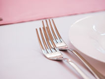 Two kitchen forks. On dinner table with pink tablecloth Stock Images
