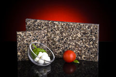 Two kitchen granite countertop samples standing on glossy black table with food decoration. Kitchen counter concept. royalty free stock image