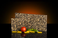 Two kitchen granite countertop samples standing on glossy black table with food decoration. Kitchen countertop concept. Royalty Free Stock Image