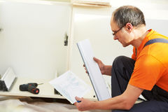 Two kitchen installers at carpenter work Stock Photos
