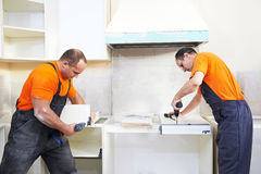 Two kitchen installers at carpenter work Royalty Free Stock Photo