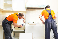 Two kitchen installers at carpenter work Stock Photo