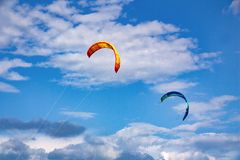 Two kites against a blue cloudy sky stock images