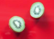 Two kiwi halves. Two kiwis on a red background royalty free stock photography