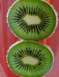 Two kiwi in mineral water. Slices of kiwi partially submerged in mineral water bubbles Royalty Free Stock Photography