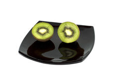 Two kiwis on a black plate, the top view. The isolated white background royalty free stock images
