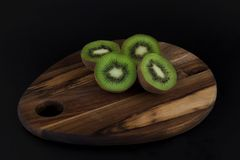 Kiwis on wooden cutting board. Two kiwis cut in half on wooden board and black background royalty free stock image