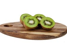 Kiwis on a wooden cutting board. Two kiwis cut in half on a wooden cutting board royalty free stock photography