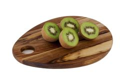 Kiwis on a wooden cutting board. Two kiwis cut in half on a wooden cutting board stock images