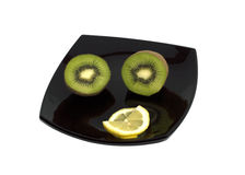 Two kiwis and segments of a lemon on a black plate, the top view. The isolated white background stock photos