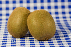 Two kiwis on the table. Two kiwis fruits isolated on the kitchen table stock photography