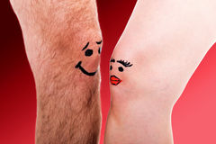 Two knees falling in love. In front of red background Royalty Free Stock Photo
