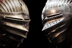 Two knights. Isolated two knights on the black background with steel helmets Stock Photos