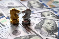 Two knights chess stand against each other on Us dollar banknote. Money game concept. Copy space play playing finance business economy competition strategy royalty free stock photo