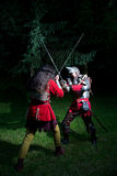 Two Knights Fencing in the Woods at Night Stock Photography