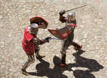 Two knights fighting. Aerial view of two knights fighting with swords and shields, cobblestone background Royalty Free Stock Photos