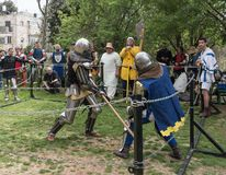 Two knights with halberds fight in the ring at the Purim festival with King Arthur in the city of Jerusalem, Israel stock image