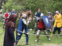 Two knights with shields and swords fight in the ring at the Purim festival with King Arthur in the city of Jerusalem, Israel stock images