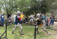 Two knights with swords fight in the ring at the Purim festival with King Arthur in Jerusalem city, Israel royalty free stock images