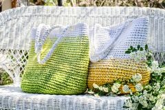 Two knitted hand-made bags in yellow, green and white colors stays on white  wicker couch in the garden with blooming spirea stock images