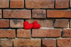 Two knitted heart on a crumbling old red brick textured wall. Two knitted red heart on a crumbling old red brick textured wall is masonry Royalty Free Stock Photography