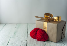 Two knitted hearts, gift box on rustic background Royalty Free Stock Images