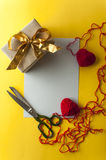Two knitted hearts, gift box on yellow background Royalty Free Stock Photography
