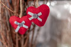 Two knitted hearts hanging on a branch. Symbol of love and Valentine`s day celebratione. Toned foto.  royalty free stock images