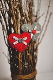 Two knitted hearts hanging on a branch. Symbol of love and Valentine`s day celebratione. Toned foto.  stock images