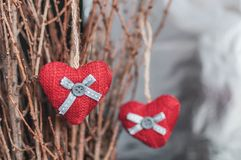 Two knitted hearts hanging on a branch. Symbol of love and Valentine`s day celebratione. Toned foto.  stock photography