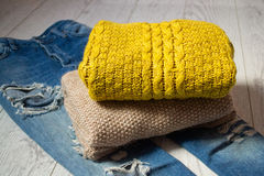 Two knitted sweaters on torn jeans, a wooden background. Fashionable concept, side view Stock Photos