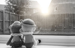 Two knitting dolls boy and girl holding hand sitting next to the window, Black and white colour. Two knitting dolls boy and girl holding hand sitting next to the Royalty Free Stock Image