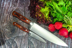 Two knives with vegetables. On wood background stock photo