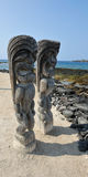 Two Kona wood ocean front beach tikis Stock Photography