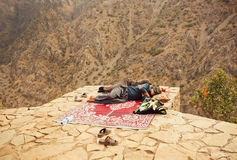 Two kurdish men sleeping over a precipice in mountaine village Royalty Free Stock Photo
