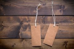 Two lables hanging from string ties against a wooden wall. Blank tags ready for text or other concept writing for business or finance Stock Photos