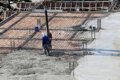Two labor work pouring liquid concrete from cement mixer to buil Stock Photo