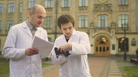 Two laboratory assistants discuss something at university background stock footage
