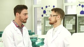 Two laboratory technicians communicate on working subjects. Two guys are conducting dialogues on the topic of work. They stand in the middle of the lab. Lab stock footage
