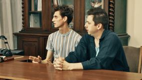 Two laborers get berated by boss at office with wood bookcase on background stock footage
